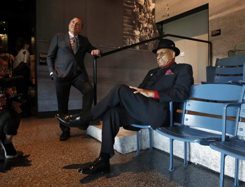 FILE - In this Oct. 3, 2018, file photo, Hockey Hall of Famer Willie O'Ree, right, who was the first African-American hockey player in the NHL, sits b