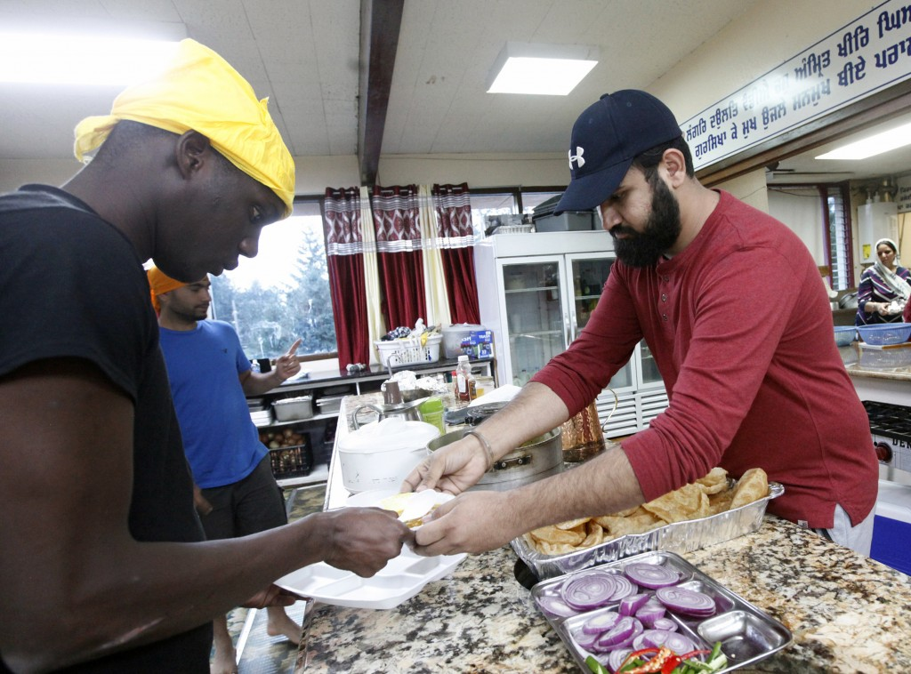In this Wednesday, Oct. 3, 2018, photo, Karandeep Singh, right, serves a bowl of curry to Abdoulaye Camara at the Dasmesh Darbar Sikh temple in Salem,