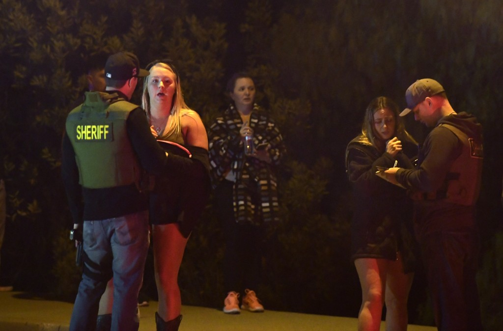Sheriff's deputies speak to potential witnesses as they stand near the scene of a mass shooting Thursday, Nov. 8, 2018, in Thousand Oaks, Calif., wher
