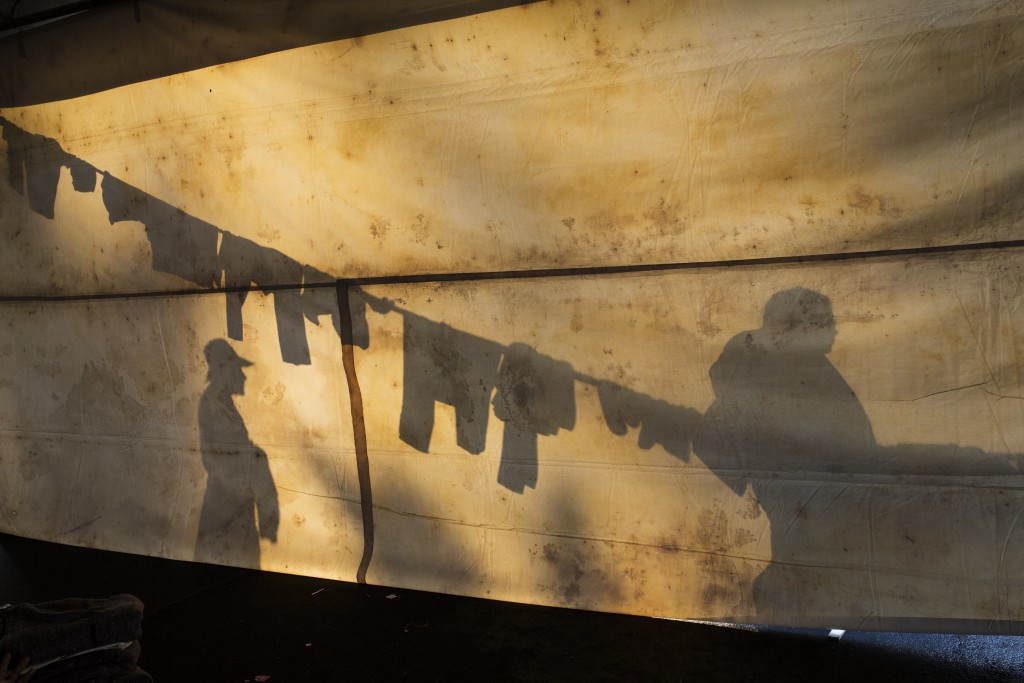 In this Nov. 6, 2018 photo, the silhouettes of Central American migrants are projected on the side of a tent at the Jesus Martinez stadium in Mexico C