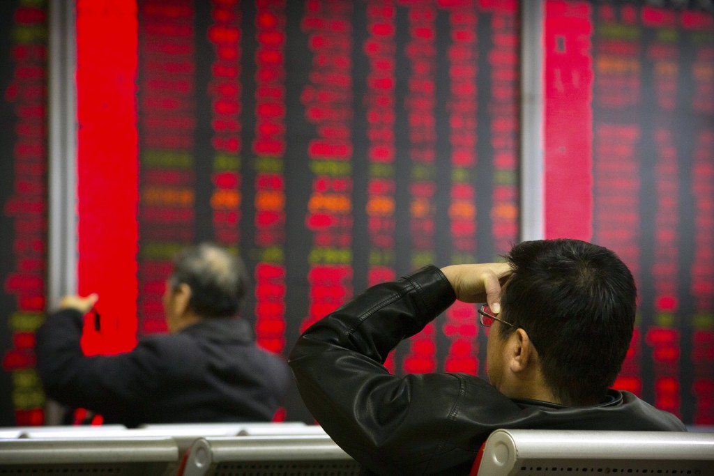 In this Oct. 31, 2018, photo, Chinese investors monitor stock prices at a brokerage house in Beijing. China's government is trying to dispel stock mar