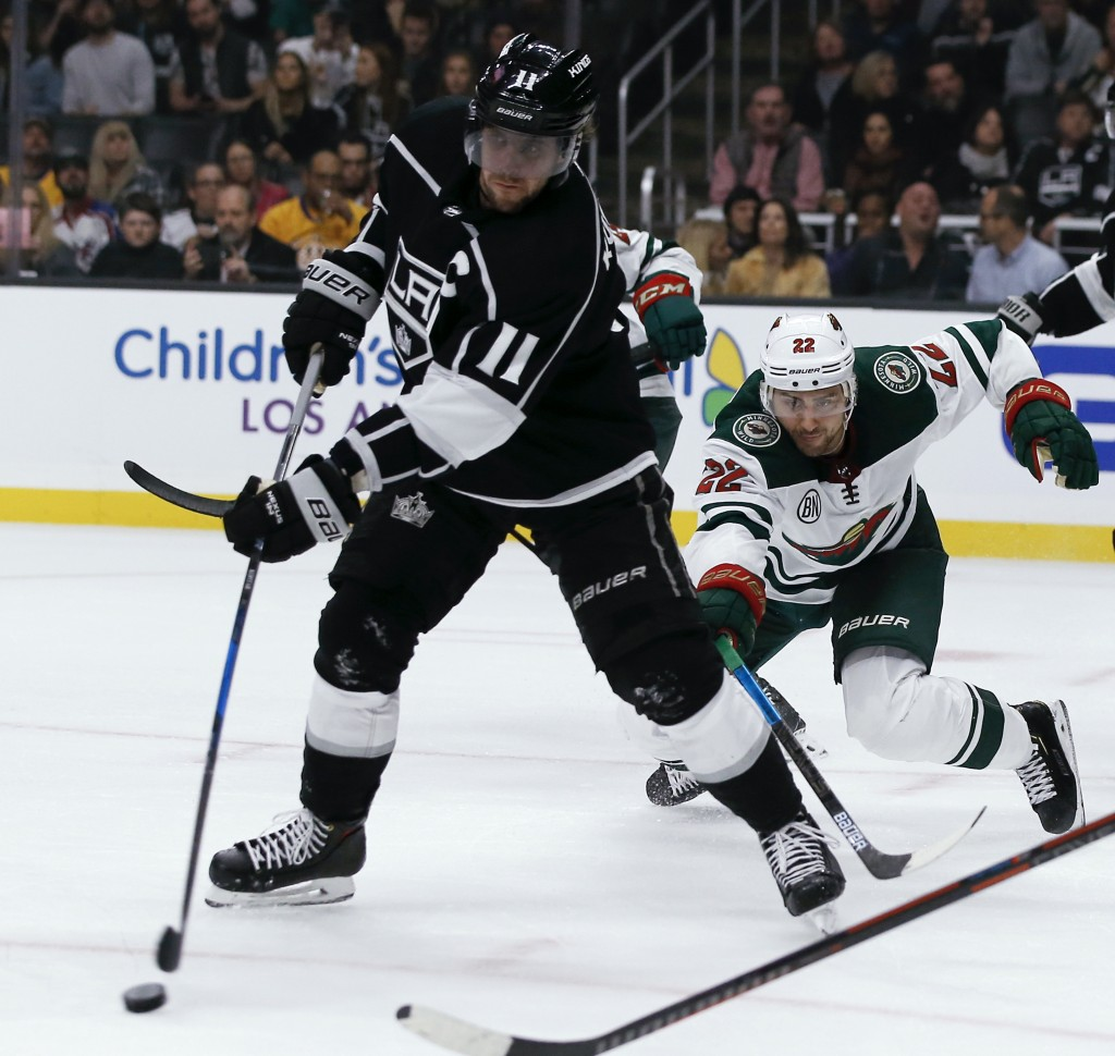 Los Angeles Kings center Anze Kopitar (11), of Slovenia, clears the puck under pressure from Minnesota Wild right wing Nino Niederreiter (22), of Swit