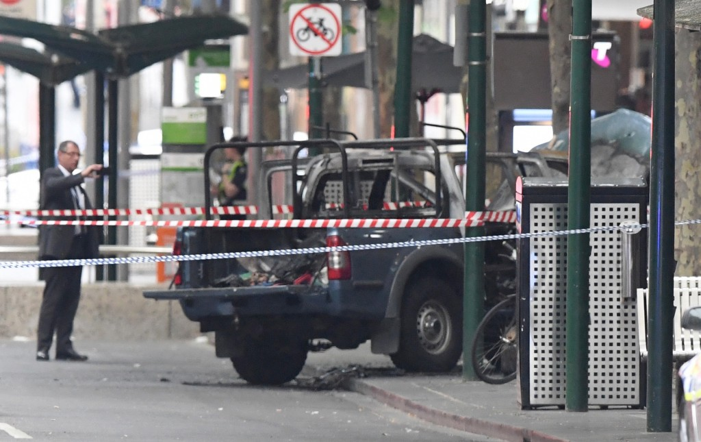 A burnt out vehicle is seen on Bourke Street in Melbourne, Friday, Nov. 9, 2018. A knife-wielding man stabbed two people, one fatally, in Australia's