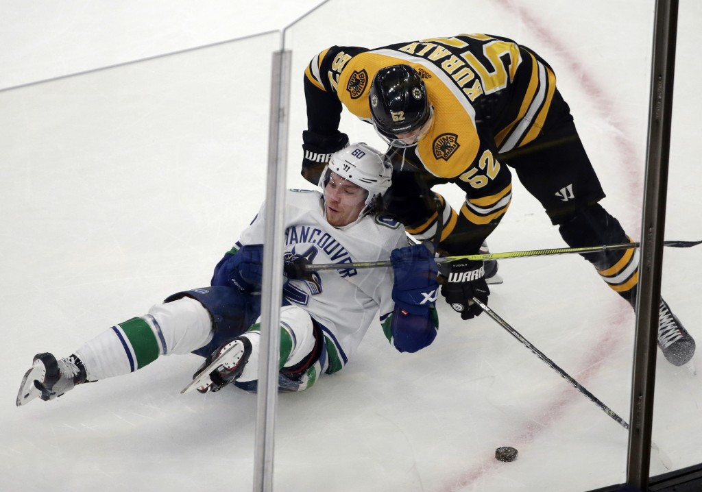 Vancouver Canucks center Markus Granlund (60) and Boston Bruins center Sean Kuraly (52) compete for the puck during the third period of an NHL hockey