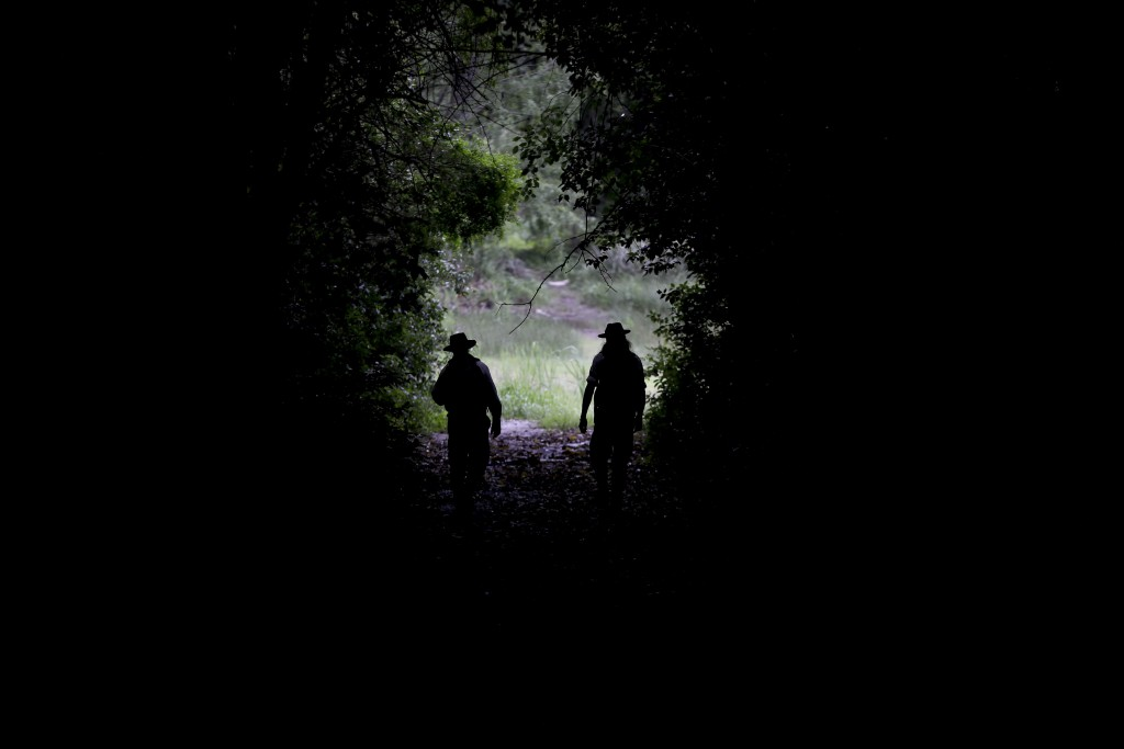 "In this Oct. 18, 2018 photo, park rangers Agustin Mezzabotta, right, and Gonzalo Alves walk at ""Ciervo de los Pantanos"" National Park near Buenos Aire"