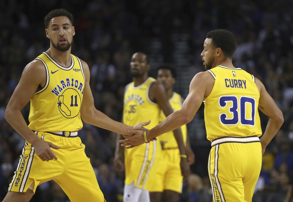Golden State Warriors' Klay Thompson, left, and Stephen Curry (30) celebrate a score against the Milwaukee Bucks during the first half of an NBA baske