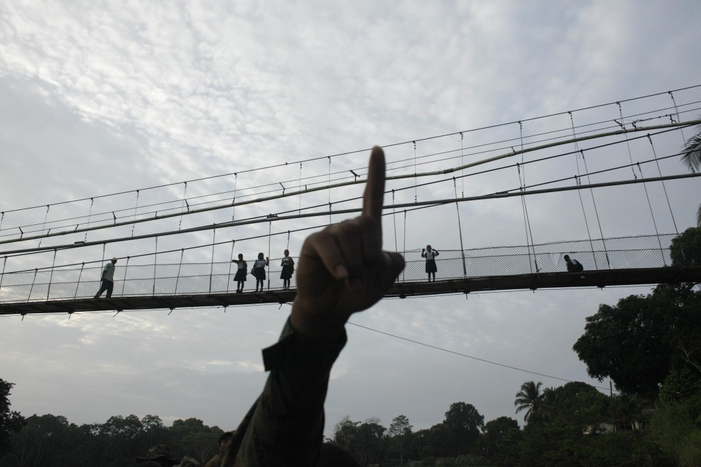 FILE - In this June 19, 2012, file photo, a Panama border police officer points as he begins to patrol in the Darien Province, on the border with Colo