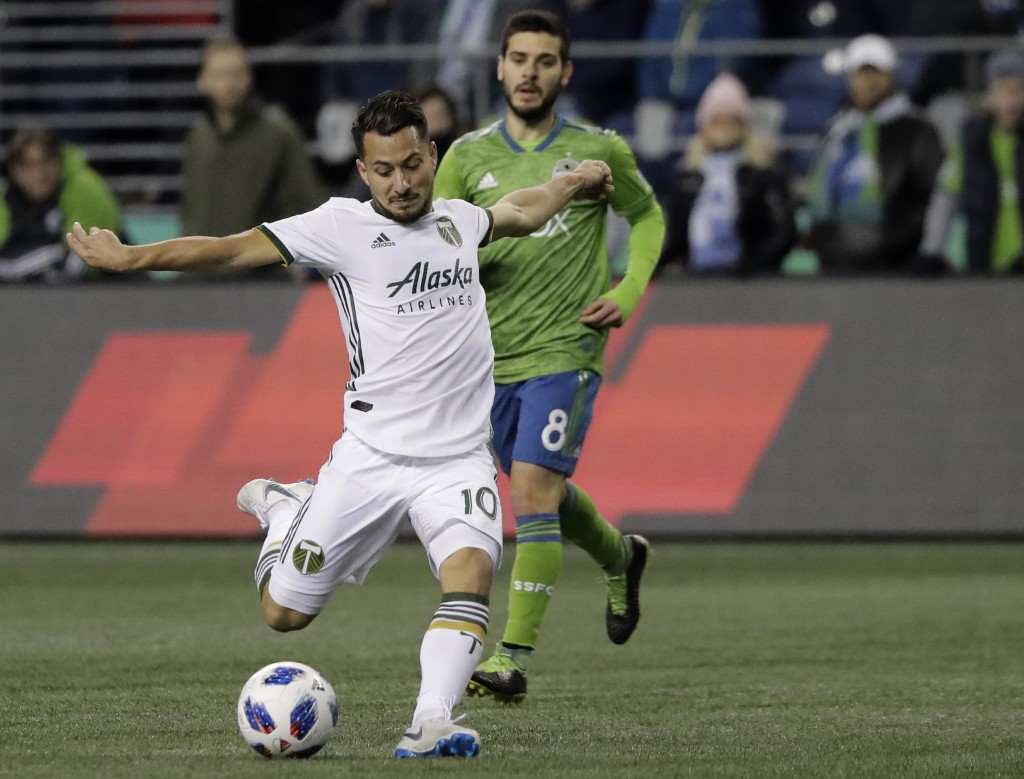 Portland Timbers midfielder Sebastian Blanco (10) takes a shot as Seattle Sounders midfielder Victor Rodriguez, rear, watches during the first half of