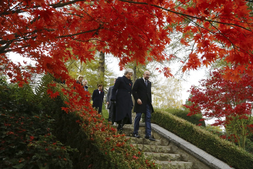 Britain's Prime Minister Theresa May and Belgian Prime Minister Charles Michel, right, walk through the St Symphorien Military Cemetery in Mons, Belgi...