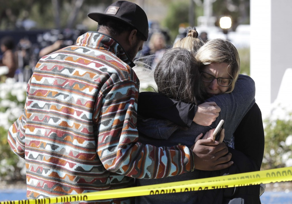 Mourners embrace outside of the Thousand Oaks Teen Center, where relatives and friends gathered in the aftermath of a mass shooting, Thursday, Nov. 8,