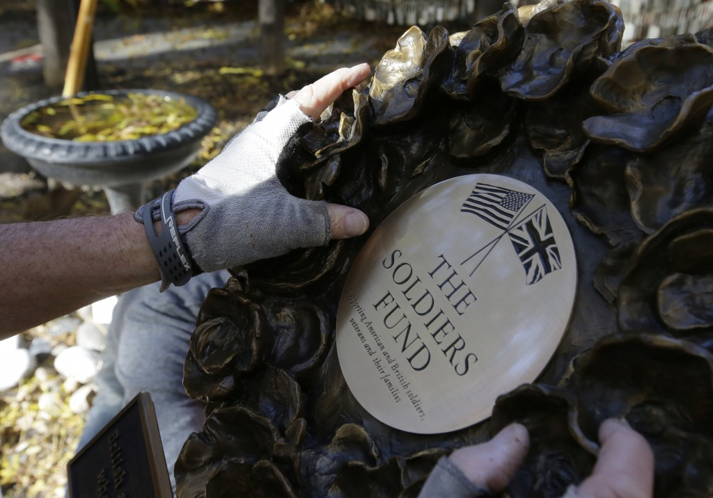 In this Wednesday, Nov. 7, 2018 photo James Re, of Boston, hands only, positions a bronze wreath as it becomes part of a memorial on the grounds of Ol
