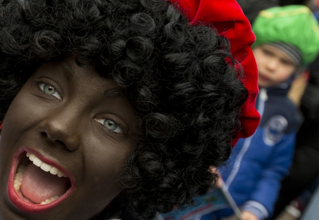 In this Saturday, Nov. 12, 2016 file photo, a Black Pete interacts with children during the arrival of Sinterklaas in Maassluis, Netherlands, Saturday