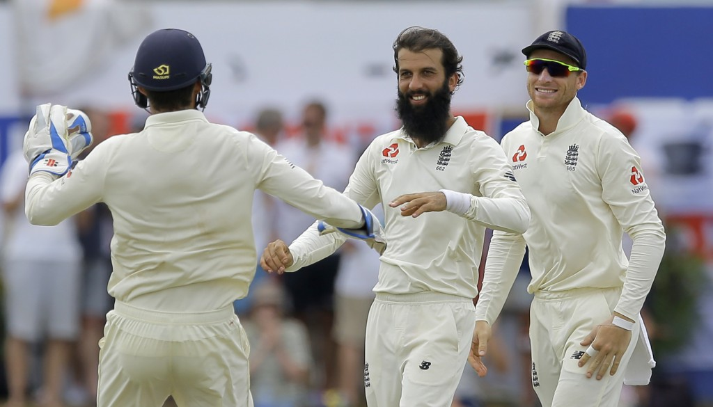 England's Moeen Ali, center, celebrates the wicket of Sri Lanka's Dimuth Karunaratne with Joss Buttler, right, and Ben Foakes during the fourth day of