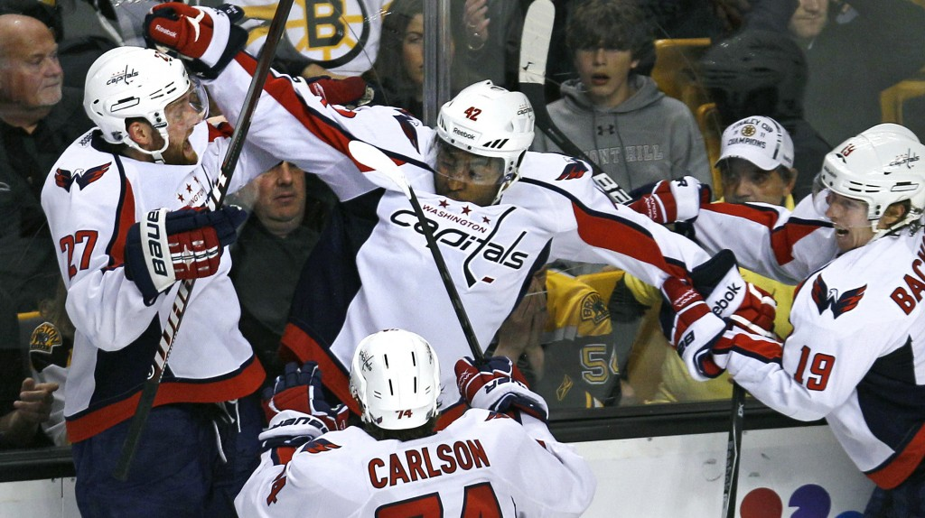 FILE - In this April 25, 2012, file photo Washington Capitals right wing Joel Ward, center, is congratulated by teammates after scoring the game-winni