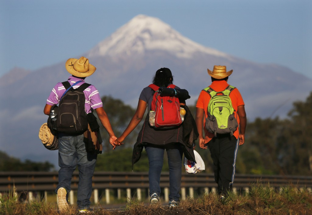 In this Nov. 5, 2018 photo, Central American migrants begin their morning trek facing Pico de Orizaba volcano as part of a thousands-strong caravan ho