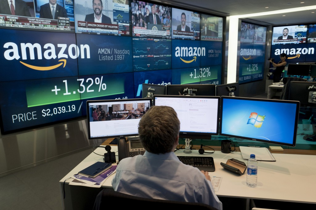 FILE- In this Sept. 4, 2018, file photo a Nasdaq employee monitors market activity in New York. Companies around the country and across industries are