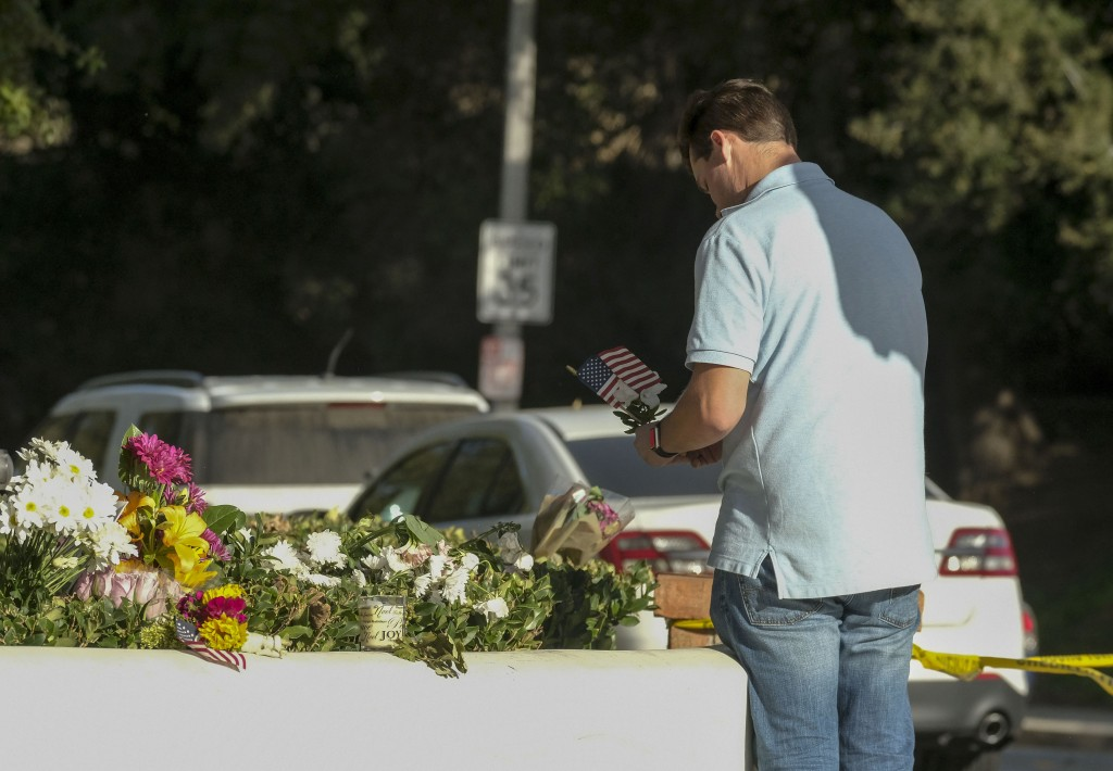 Brian White places a U.S. flag with a flower near the scene of a mass shooting Thursday, Nov. 8, 2018, in Thousand Oaks, Calif., after a gunman opened...