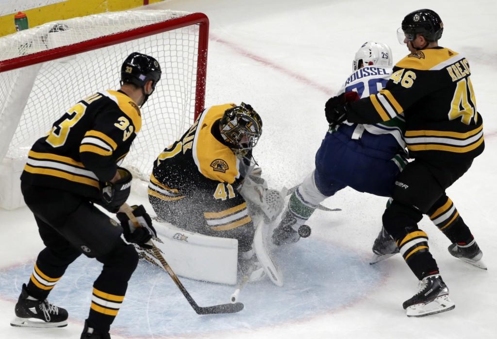 Boston Bruins goaltender Jaroslav Halak (41) makes a save on a shot by Vancouver Canucks left wing Antoine Roussel (26) as Bruins center David Krejci