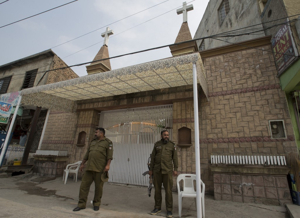 In this Nov2, 2018, photo, Pakistani police officers stand guard outside a church in Rawalpindi, Pakistan. The uproar surrounding Aasia Bibi _ a Pakis