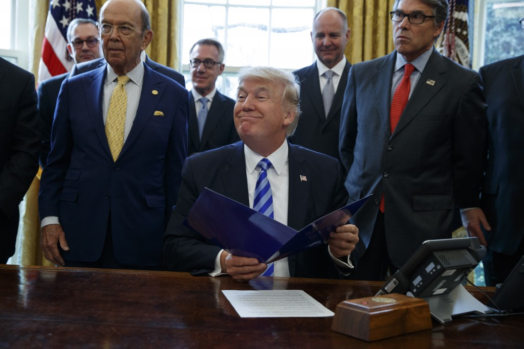 FILE - In this March 24, 2017 file photo, President Donald Trump, flanked by Commerce Secretary Wilbur Ross, left, and Energy Secretary Rick Perry, is