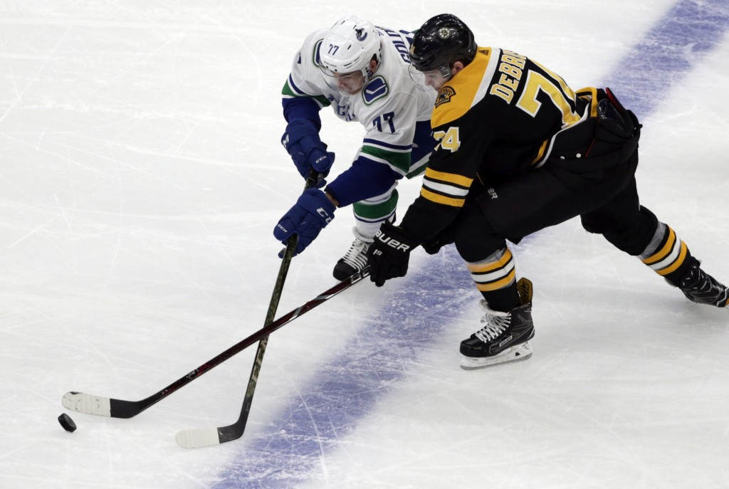 Vancouver Canucks right wing Nikolay Goldobin (77) and Boston Bruins left wing Jake DeBrusk (74) compete for the puck during the first period of an NH