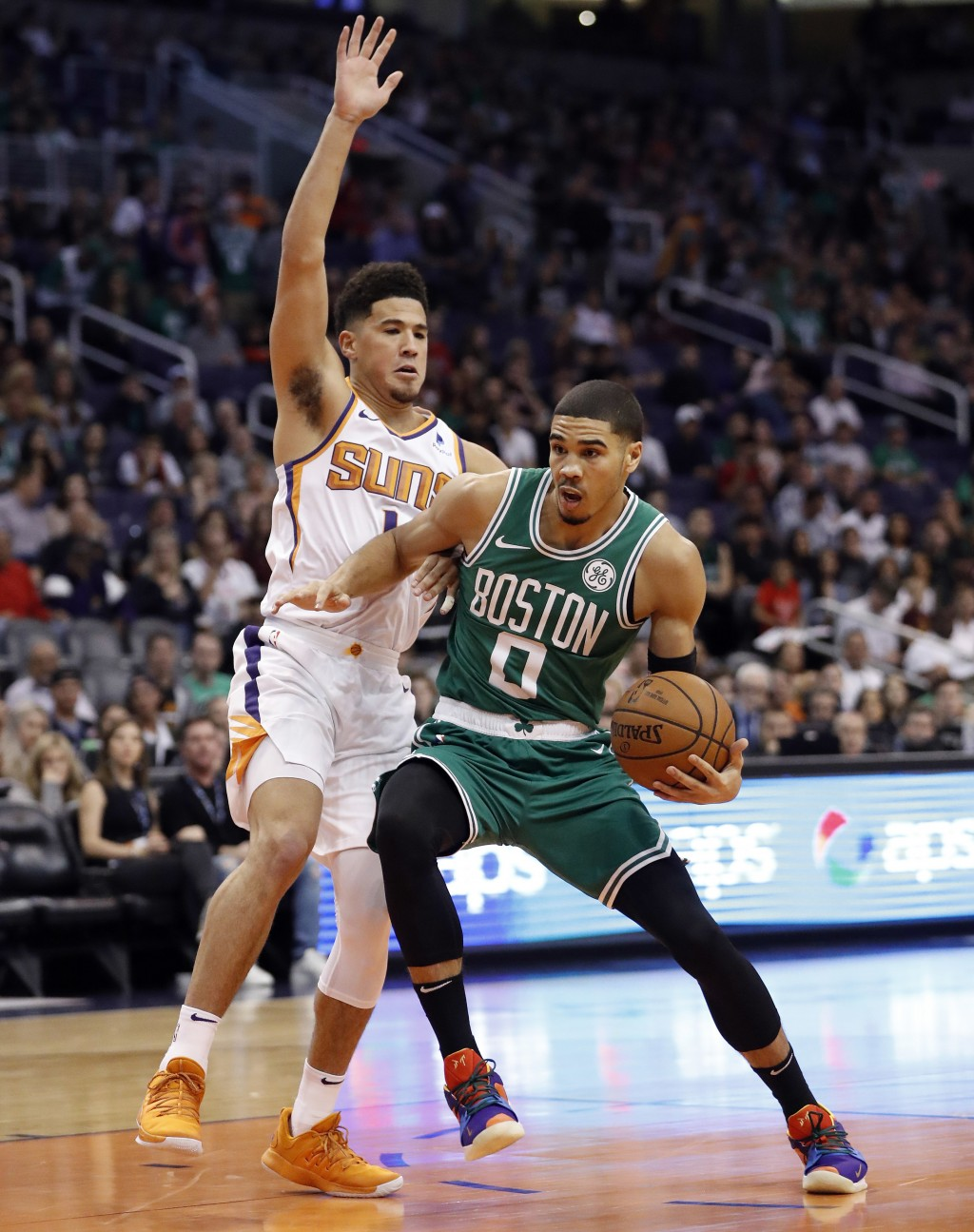 Boston Celtics forward Jayson Tatum (0) drives past Phoenix Suns guard Devin Booker (1) during the first half of an NBA basketball game Thursday, Nov.