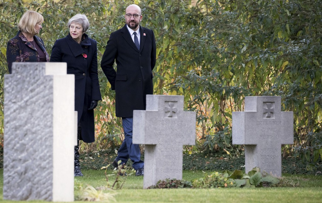 British Prime Minister Theresa May, center, and Belgian Prime Minister Charles Michel, right, walk among graves before laying wreaths at the graves of...