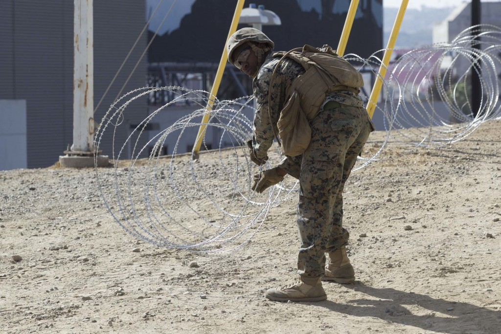 In a Nov. 6, 2018 photo, Marine Corps engineers from Camp Pendleton put up razor wire just east of the San Ysidro Port of Entry where trains pass from