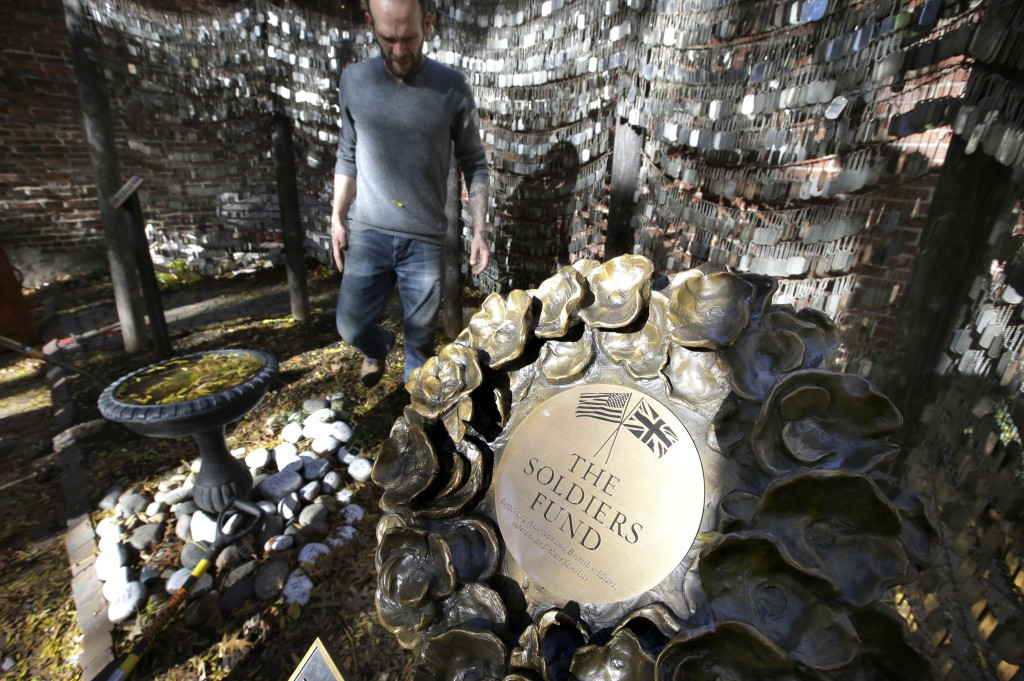In this Wednesday, Nov. 7, 2018 photo Tim Wenrich, of Boston, caretaker at Old North Church, stands near a bronze wreath, right, that is part of a mem