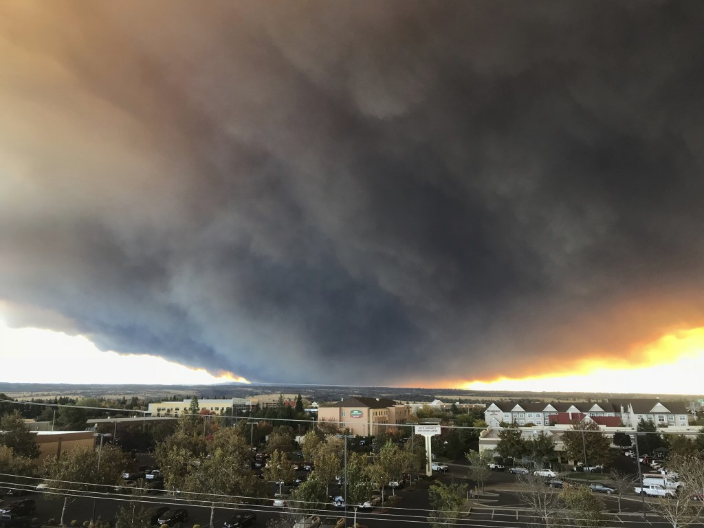 The massive plume from the Camp Fire, burning in the Feather River Canyon near Paradise, Calif., wafts over the Sacramento Valley as seen from Chico,
