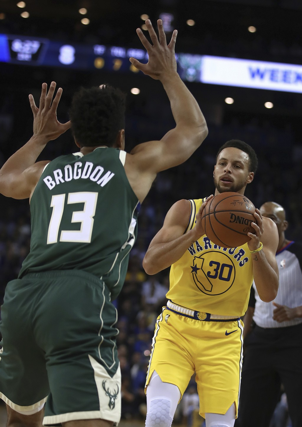 Golden State Warriors' Stephen Curry, right, looks to shoot against Milwaukee Bucks' Malcolm Brogdon (13) during the first half of an NBA basketball g