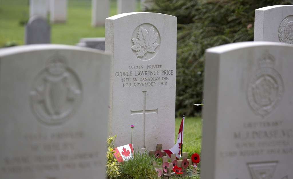 FILE - In this July 26, 2014, file photo, wooden crosses and Canadian flags adorn the grave of World War I Canadian soldier Pvt. George Lawrence Price
