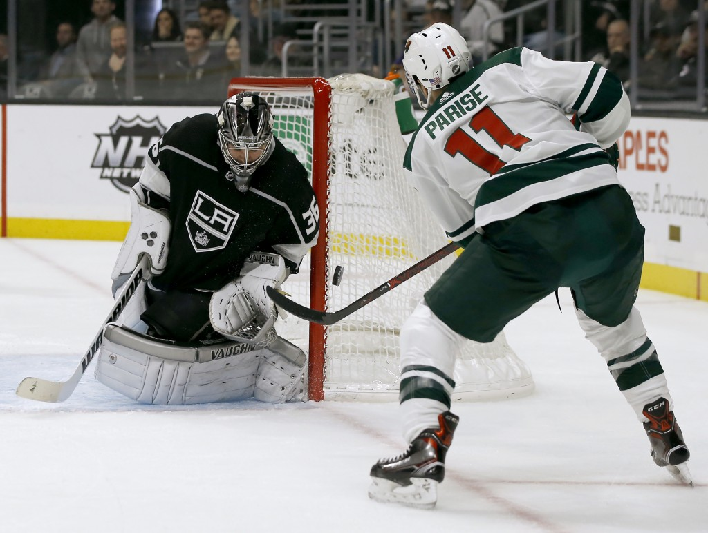 Los Angeles Kings goaltender Jack Campbell, left, deflects a shot by Minnesota Wild left wing Zach Parise during the first period of an NHL hockey gam