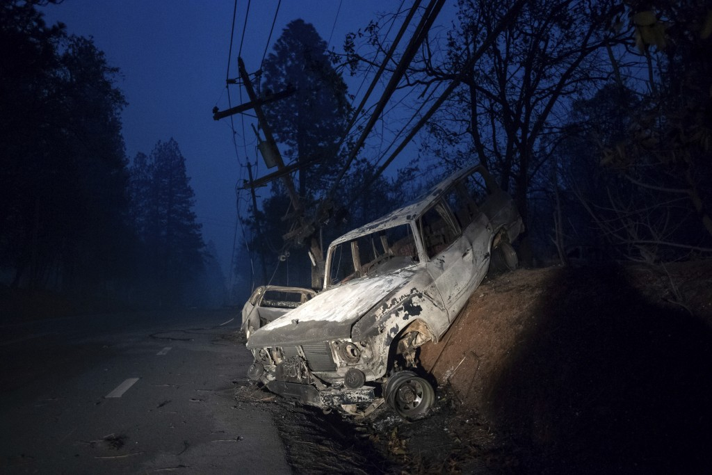 A scorched vehicle rests on a roadside as the Camp Fire tears through Paradise, Calif., on Thursday, Nov. 8, 2018. Tens of thousands of people fled a