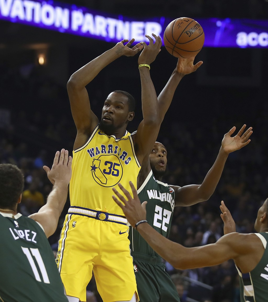 Milwaukee Bucks' Khris Middleton (22) steals the ball from Golden State Warriors' Kevin Durant (35) during the first half of an NBA basketball game Th