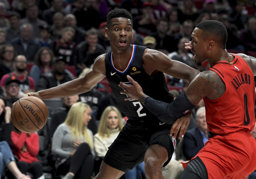 Los Angeles Clippers guard Shai Gilgeous-Alexander, left, tries to get past Portland Trail Blazers guard Damian Lillard, right, during the first half