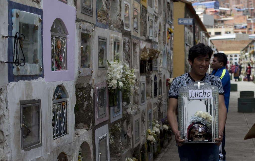 A man carries a decorated human skull after praying at the General Cemetery during the Natitas Festival in La Paz, Bolivia, Thursday, Nov. 8, 2018. Ce