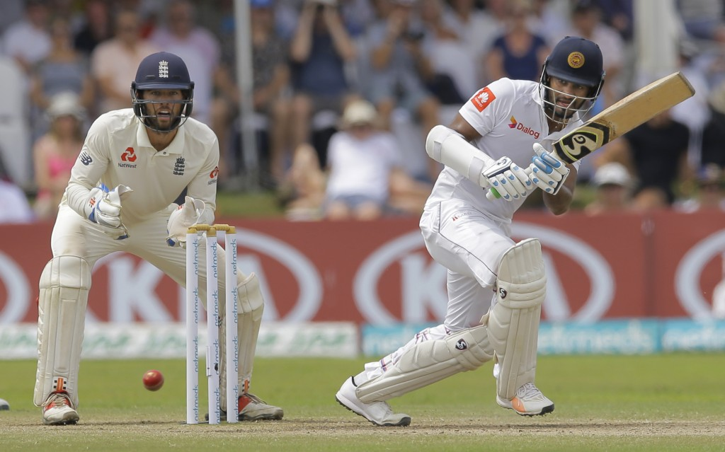 Sri Lanka's Dimuth Karunaratne plays a shot as England's Ben Foakes watches during the fourth day of the first test cricket match between Sri Lanka an