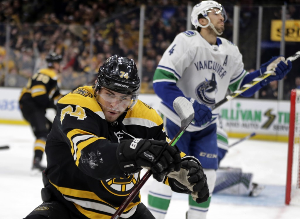 Boston Bruins left wing Jake DeBrusk (74) celebrates his goal as Vancouver Canucks defenseman Michael Del Zotto (4) reacts during the second period of