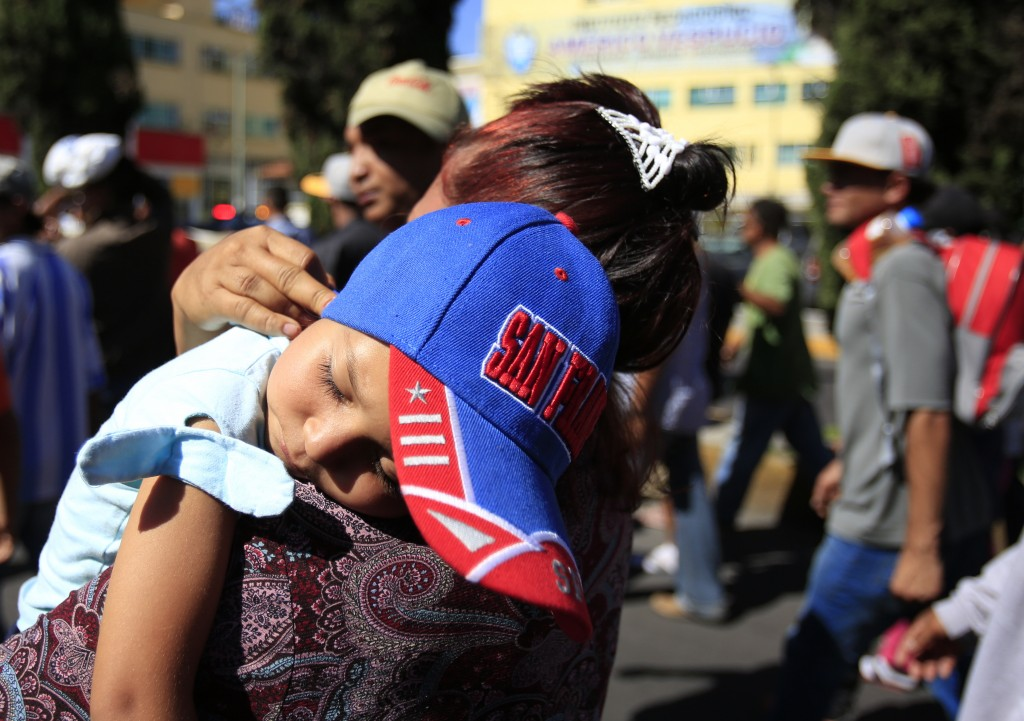 A sleeping Honduran girl is carried as a group of Central American migrants, representing the thousands participating in a caravan trying to reach the...