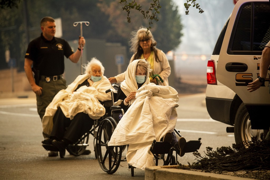 Emergency personnel evacuate patients as the Feather River Hospital burns while the Camp Fire rages through Paradise, Calif., on Thursday, Nov. 8, 201