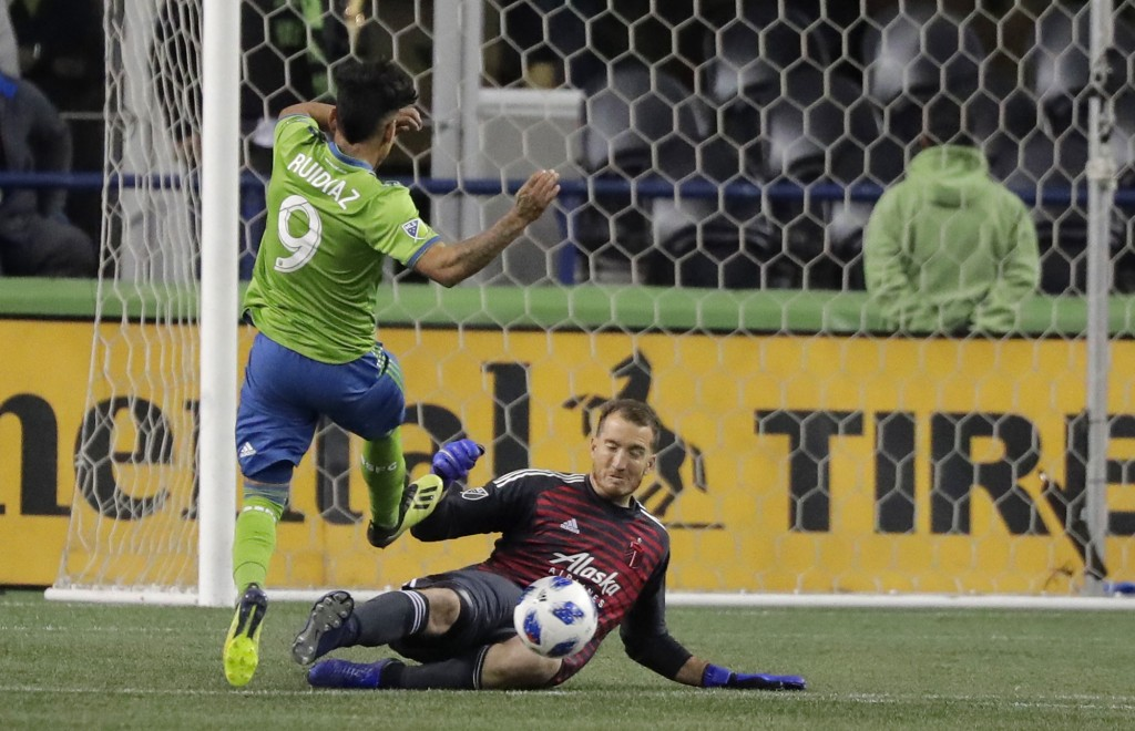 Seattle Sounders forward Raul Ruidiaz (9) has a shot deflected by Portland Timbers goalkeeper Jeff Attinella during the first half of the second leg o