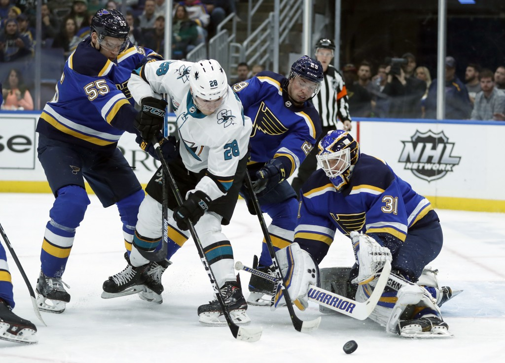 San Jose Sharks' Timo Meier (28), of Switzerland, is unable to score past St. Louis Blues goaltender Chad Johnson (31) as Blues' Colton Parayko (55) a...