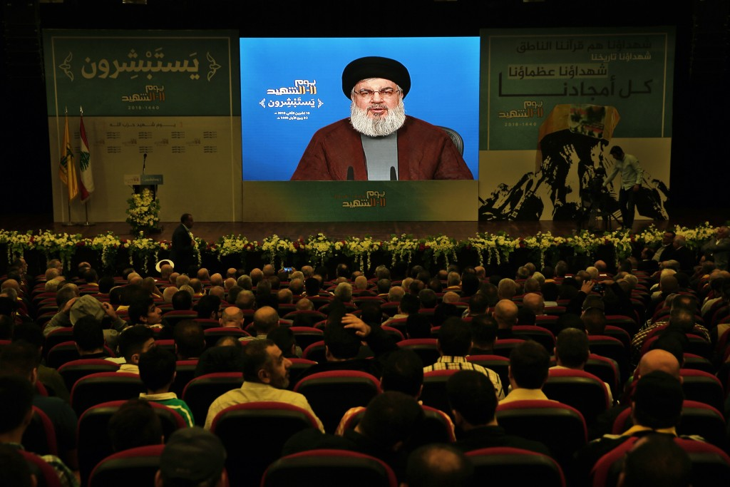 Supporter of the Iranian-backed Hezbollah group listen to a speech of Hezbollah leader Sayyed Hassan Nasrallah, via a video link, during a rally marki