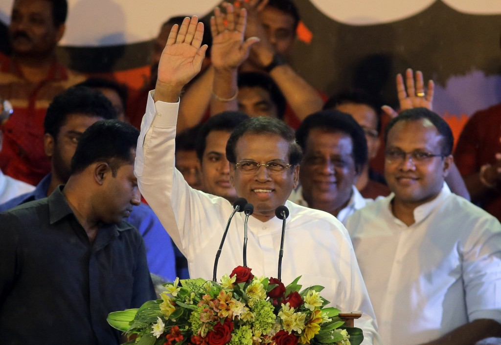 FILE - In this Nov. 5, 2018, file photo, Sri Lankan President Maithripala Sirisena, center, waves to supporters during a rally outside the parliamenta