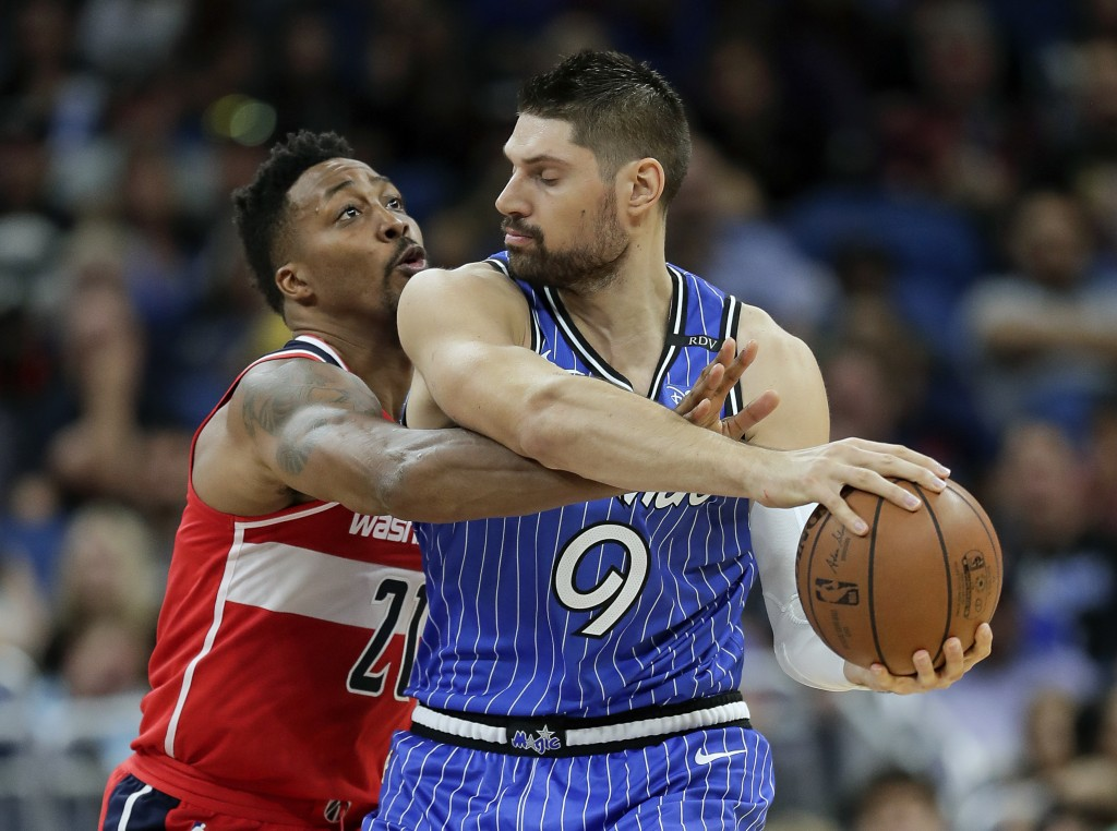 Washington Wizards' Dwight Howard, left, fouls Orlando Magic's Nikola Vucevic (9) as he goes for the ball during the first half of an NBA basketball g