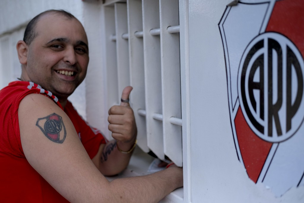 In this Nov. 7, 2018 photo, Matias Chamorro, a 33-year-old lifelong fan of River Plate club, poses for a picture showing his club tattoo while he pays