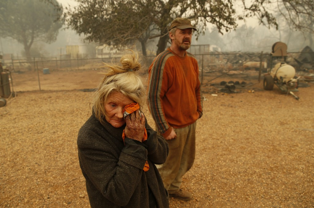 Cathy Fallon wipes her face beside her son Gabriel Fallon as she stands near the charred remains of her home Friday, Nov. 9, 2018, in Paradise, Calif.