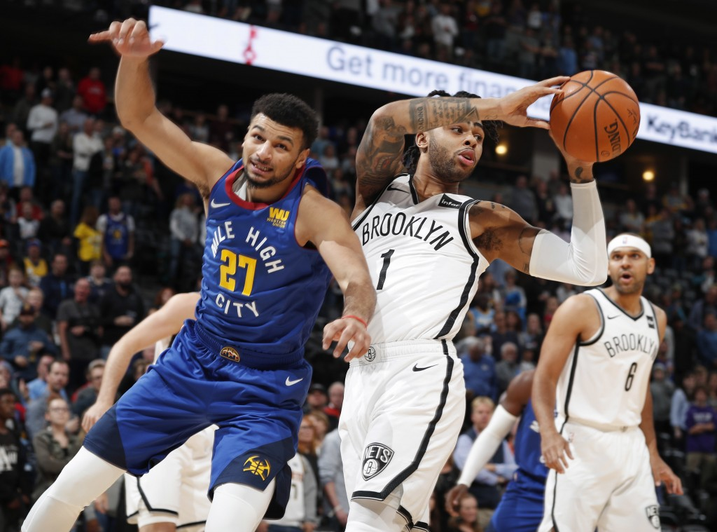 Brooklyn Nets guard D'Angelo Russell, right, pulls in a rebound as Denver Nuggets guard Jamal Murray covers in the first half of an NBA basketball gam
