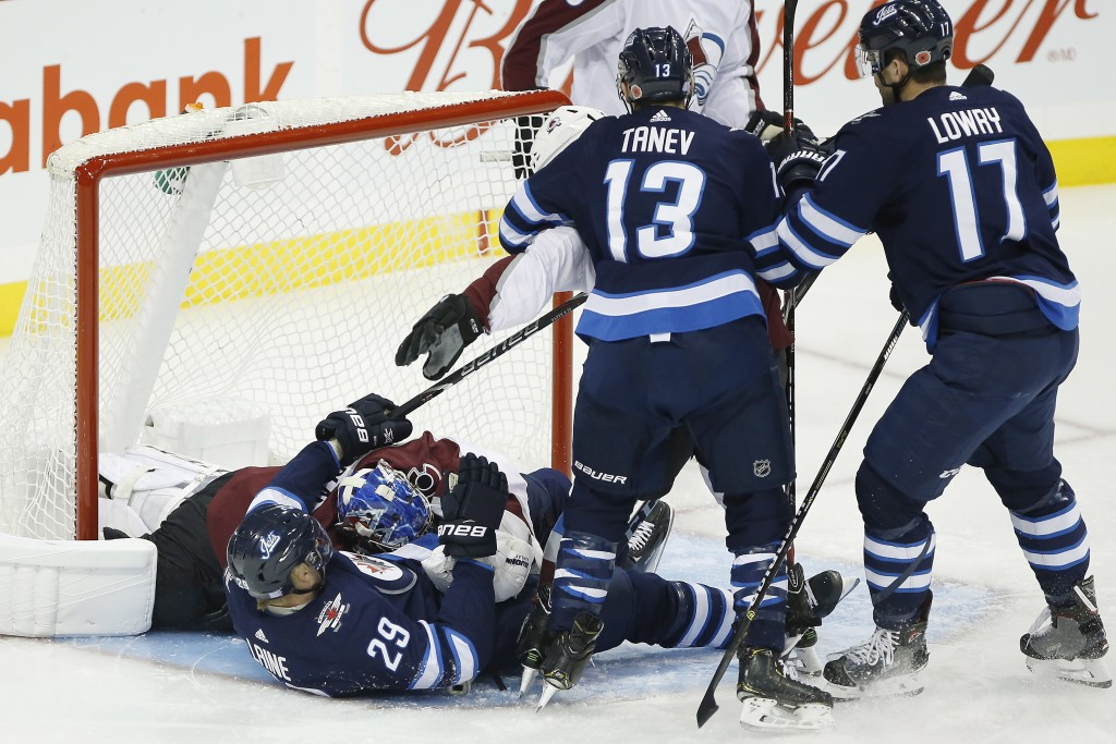 Colorado Avalanche goaltender Semyon Varlamov (1) lands on Winnipeg Jets' Patrik Laine (29) after saving his shot during the first period of an NHL ho